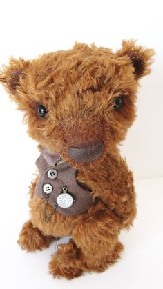 Theophilus (Teofilis) is 26cm bear, made of special bear materials, has got glass eyes, 5 joints (double for the head), embroidered and waxed nose, shaded with oil paint, stuffed with steel pellets and fibrefilling. His arms are wired and he is designed to stand. Theophilus wears a cotton double sided vest, a linen tailcoat and has a clock pendant, can be fully undressed.