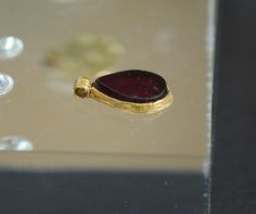 Grave goods from the 7thC Anglo-Saxon cemetery at Saltwood, Kent. Grave 3. Garnet pendant in gold mount. Photograph courtesy of Lindsay Kerr.