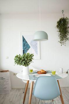 Bright Mid Century Modern dining room with graphic artwork, white walls, and hanging plants.
