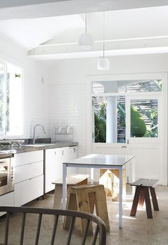 The sun-filled kitchen is mostly white with exposed timber beams accentuating the space's height. | A 1914 Durban home is transformed for the 21st century | Inside Out - JUL18 | Design: Koop Design | Photography Elsa Young