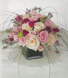 #centerpiece of assorted #roses in #white, #pink and #fuschia hues accented with bear grass and limonium