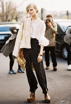 White blouse with bell sleeves, printed pants, and gold clutch