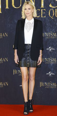 ICharlize Theron fused edge and professionalism at The Huntsman & The Ice Queen photocall in a tough button-front leather Reformation mini skirt that she elevated with a white lace top, a sleek tux blazer, Anita Ko earrings, and cool open-toe booties.
