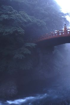 Sacred Shin-kyo Bridge, Nikko, spans the Daiya River. Its simple elegance was, during feudal times, only to be crossed by the emperor. Considered one of the most beautiful structures in Japan, here it seems to disappear naturally into the misty forest.