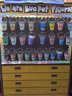 I made my buckets with clear plastic solo cups and then hole punched them and made a little handle from glittery sparkly wire stuff. The kids decorated, cut, and glued the front of their buckets. If you have a cabinet like this, I have an idea for you!! I bought cork board tiles from Target (4 for $1) and then stuck them up here and now I can staple to the wall without damaging the cupboard. Yay!