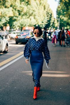 This look is a study in layering, from the cream turtleneck to the printed collared dress to the navy pencil skirt worn on top. And we can't forget about these fiery red booties. This show-goer proves that fashion is not about playing it safe.