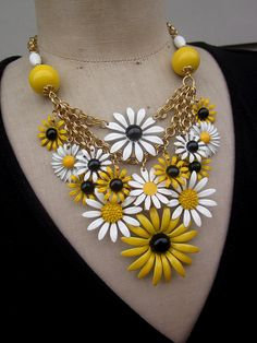 This statement necklace is gorgeous! It is comprised of 15 matching vintage enamel daisy earrings and brooches. Circa 1960s and 70s, I have removed their pins and attached them as charms from 3 tiers of vintage brass chain. The neck is finished with vintage lucite beads, more brass chain, a brass parrot clasp and a brass extention chain.    The inner chain has a neck circumference of 16 inches with an additional 2.5 inches of extension chain. To give you an idea of the size of the pieces…