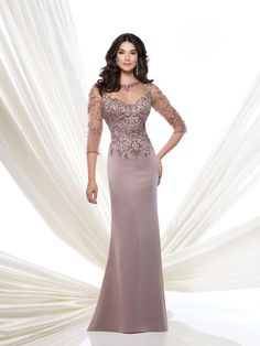 Crepe slim A-line gown with hand-beaded illusion three-quarter length sleeves, beaded illusion jewel neckline over sweetheart bodice with illusion keyhole back, sweep train, suitable for the mother of the bride and the mother of the groom. Embellish by David Tutera earring style Monica and bracelet style Jacqueline Bangle sold separately. Sizes: 4 – 20