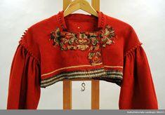 Trøyen er sydd med armsøm rundt skulder og hals. Insatt med sikksakk-klippet  rodt klede samme som hovedstoff. Rolorkant rundt armringningen. Nederst på trøyen er påsatt et stripet bånd i vevet ull. Armene er rynket oppe.  Trøyen er rød med rosesøm og perler. Bell Sleeves, Bell Sleeve Top, Hand Embroidery, Band, Tops, Women, Fashion, Moda, Sash