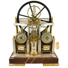 A French Industrial Steam-Engine Form Weather Station  France  circa 1870  A good French industrial series gilt and silvered brass miniature steam-engine form weather station with a large flywheel and piston, the brickwork furnaces housing the timepiece and barometer in drums flanking a central thermometer, raised on rouge marble plinth.        The series of French Industrial clocks were made at the end of the 19th century in response to the ongoing Industrial Revolution and the public…