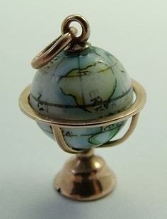 A 1940s 9ct rose gold charm with a rotating painted porcelain globe.