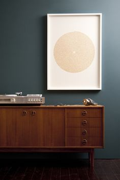I love the color scheme going on here. Mid century wood looks so good against that dark blue.