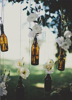 Hang flowers in bottles from the trees