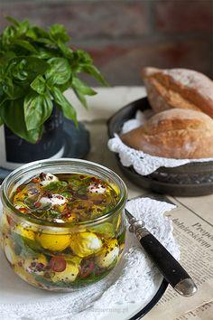 """Kulki mozarelli marynowane w oliwie z dodatkiem ulubionych, świeżychziół. Warto mieć je w lodówce!  Doskonale sprawdzą się jako dodatek do letnich sałatek, surówek, kanapek lub """"atrakcja"""" na desce serów. Sos, w którym marynujemy kulki mozarelli jest pyszny. Używajcie go dosałatek, na chleb, do marynowania warzyw i mięs. Polecam!   SKŁADNIKI:   opakowanie minimozzarelli  0,5 papryczkichili  3-4 ząbki czosnku  ziarenka kolorowego pieprzu  szczypta soli  oliwa z oliwek  świeże…"""