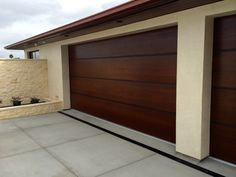 Interesting garage doors for you guys to think about. African Mahogany Contemporary Wood Garage Door with Anodized Aluminum Bands - Tungsten Royce 1