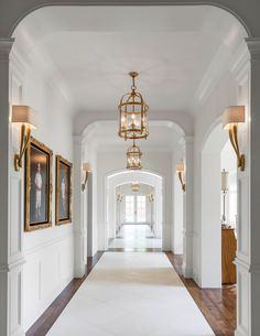 A long hallway features walls clad in wainscoting lined with kids' photos in gold baroque frames illuminated by antique brass sconces, Ruhlmann Single Sconces, as well as round brass lanterns, Round Edwardian Entry Lanterns. Design Entrée, Flur Design, House Design, Interior Design, Lobby Design, Design Ideas, Interior Door, Hallway Chandelier, Hallway Lighting