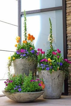 Osterdeko Idee. Blumen, besonders Tulpen, mit viel Grün und Pflanzen unterschiedlicher Höhen in schlichten Blumentopf pflanzen.