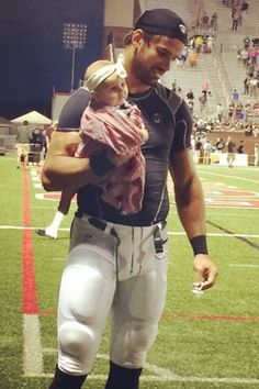 Eric Decker and his daughter Vivianne Rose Decker on the football field.