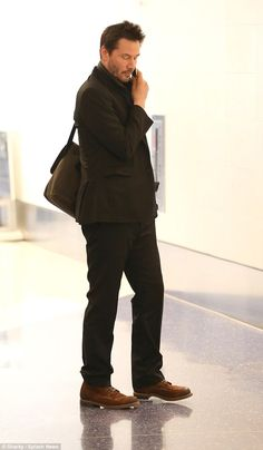2015 January 25th.  Keanu Reeves juggled his phone and luggage cart as he checked into his departing flight headed to the Sundance Film Festival in Park City, Utah.