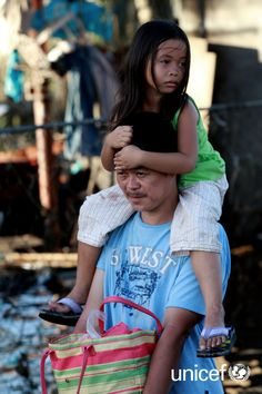 A man carries his daughter as they walk in the city of Tacloban, Leyte, Philippines. UNICEF is rushing emergency supplies to areas of the Philippines ravaged by Super Typhoon Haiyan (local name Yolanda). Cebu, Leyte, Filipino, Couple Photos, Children, Travel, Culture, Philippines, First Aid
