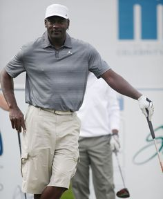 Michael Jordan Photos Photos - NBA legend Michael Jordan prepares to hit a tee…