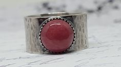 This is a beautiful specimen of rhodochrosite. The 10 millimeter stone sits pretty inside a serrated edge bezel cup.  The bezel cup (the little serrated cup that holds the stone) was carefully soldered to the main band.  Sterling silver ring band is just under 1/2 inch wide. We decided to add some fun texture to it and then antique it and hand rub with a polishing cloth to show off that texture.  The rhodochrosite cabochon is flawless. There are no cracks chips or weird spots.  This ring…