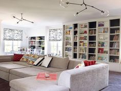 Fabulous family room features two blown glass pendants illuminating a light gray velvet pit sectional sofa placed in front of a wall of floor to ceiling sliding bookcases.