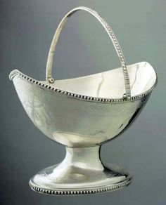Sugar Basket, date 1787, Paul Revere II (1734-1818), Boston, Massachusetts – This sugar basket was originally owned by the prominent Jewish merchant The order for this basket is listed in Revere's daybook under the date December 6, 1787. The basket displays many elements typical of the neoclassical style, with its boat shape, beaded rim & base, & floral bright-cut engraving.  The form of this basket is simple & more restrained