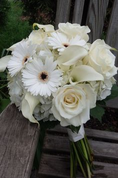 All white hand-tied bouquet, with roses, gerber daisies, calla lilies and hydrangea, created by Floribunda Designs.
