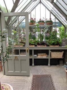 One day maybe I will have my own green house! INDOOR GARDEN :: Love love love this greenhouse! GOOD IDEA: Keep plants together on wooden trays labeled with the types of plants. | #greenhouse #greige #houseplants