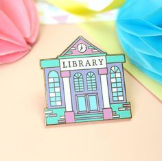 A beautiful and detailed Library enamel pin. Declare your love for books and reading, and support your local library with this cute pastel bookish pin, perfect for book lovers and readers! The pin is gold plated, with white, mint green, lilac and pink hard enamel and polished to a