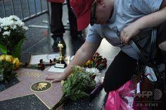 米ロサンゼルス(Los Angeles)ハリウッド(Hollywood)にあるハリウッド・ウォーク・オブ・フェーム(Hollywood Walk of Fame)のロビン・ウィリアムズ(Robin Williams)さんのプレート上にささげられた花や思い出の品々(2014年8月11日撮影)。(c)AFP/Mark RALSTON ▼12Aug2014AFP ウィリアムズさんの死を悼むファンが献花 ハリウッド http://www.afpbb.com/articles/-/3022897