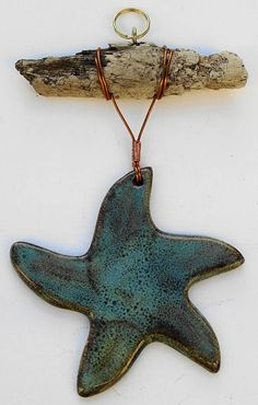 Ceramic starfish decoration attached to driftwood with copper wire. Made by us in our North Devon workshop. Glazed in our own recipe mottled green/brown glaze. We love to walk the tideline along our local beaches looking for pieces of driftwood and it seems only natural to use
