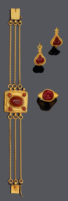 Provenance: Henri de Clercq - An antique gold and carnelian intaglio parure. Comprising a ring with a garnet intaglio, the head of a Greek young man, ca. 200 B.C., later mounted ca. 100-200 A.D., bracelet with an antique centrepiece set with a carnelian intaglio of an imperial eagle's head, ca. 200 A.D., a pair of earrings with almandine, and a gold chain set with carnelian beads and a fish pendant of carnelian, ca. 200 A.D.