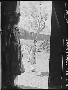 Manzanar Relocation Center, California. Yaeko Yamashita (in doorway) watches Fugiko Koba trying new pair of geta, which are stilt-like sandals especially useful in dust. They are evacuees of Japanese descent now living at this War Relocation Authority center, April 2, 1942. Photo: Department of the Interior. War Relocation Authority. Source: National Archives.