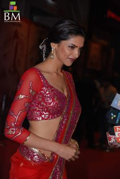 Deepika does it right in this red long-sleeved red blouse with fuchsia accents.