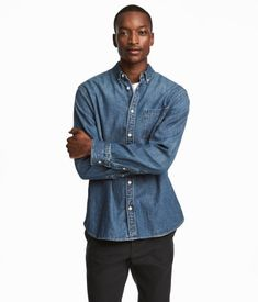 Denim blue. Shirt in washed denim with a button-down collar, buttons at front, and open chest pocket. Long sleeves with adjustable buttoning at cuffs, yoke