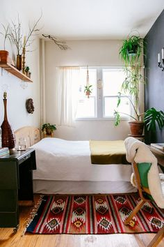 This bedroom proves that being short on space doesn't mean you have to be short on personality. Carefully curated plants, an accent wall, and a vibrant rug bring this cozy room to life.Justina Blakeney