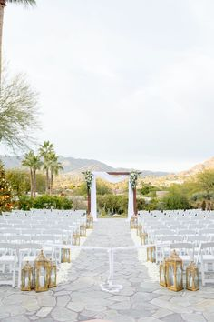 This Phoenix bride walked down an aisle lined with gold lanterns while overlooking the mountains of Arizona. You can browse hundreds of real wedding aisles and arches that fit your style on PartySlate and get inspired for your big day. Gold Lanterns, Wedding Aisles, Walking Down The Aisle, Votive Candles, Flower Petals, Arches, Tree Branches, Big Day, Floral Arrangements