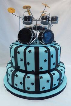 Drumkit Cake Topper - Happy Birthday to you, our band drummer! - Two tier cake with light and dark blue stripes and stars, miniature drums set on top looks realistic with cymbals and all! #cSw:) - https://www.pinterest.com/claxtonw/drummer-drumming/ - on HUMOR Pinterest Board. Fun pin via Willy van Maurik.