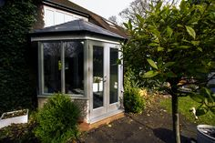 Side shot of conservatory replacement showing Rationel timber aluminium clad windows and doors in green.