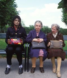 Michael Jackson and two women all with purses.