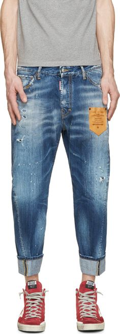 Cropped relaxed-fit jeans in deep blue. Fading, distressing, and paint splatters throughout. Six-pocket styling with stamped leather accent patch pocket at front thigh. Rolled ankle cuffs. Tonal stitching in yellow. Button fly.