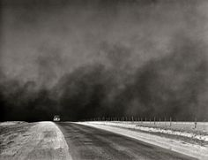 "March 1936. ""Heavy black clouds of dust rising over the Texas Panhandle"" — evidence of the forces that were driving thousands of farm families in Texas and Oklahoma to the West Coast in the great Dust Bowl migration chronicled in ""The Grapes of Wrath."""