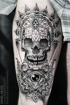 A human skull and eye are decorated with spiritual sacred geometry and mandalas in this tattoo by Daniel Meyer