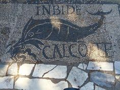 """Ostia Antica-Rome's First Port. Archaeological evidence suggests that this port was founded in the 4th century B.C. This picture is from the """"Shops of the Fishmongers"""" which sold fish. The latin wording states: """"Envious One, I Tread on You."""""""