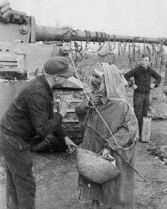 German Tiger tank crew inspect a local's food basket.