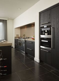 Een donkere keuken met het fornuis in een nis. Keukendealer: www.haroldlenssenkeukens.nl