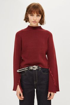 Knitted funnel neck top with wide sleeves and lattice detail.
