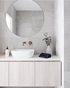 Clean lines and large format grey tile covers the floor and walls. A round frameless mirror hangs over a white sink with brass wall mounted bathroom sink faucet. The flat paneled vanity is wall mounted and has a thin white countertop Bathroom DOT + POP Wall Mounted Bathroom Sinks, Bathroom Sink Faucets, Small Bathroom, Master Bathroom, White Bathroom Wall Tiles, Light Grey Bathrooms, Bathroom Tiling, Grey Bathroom Tiles, Modern Bathroom Sink